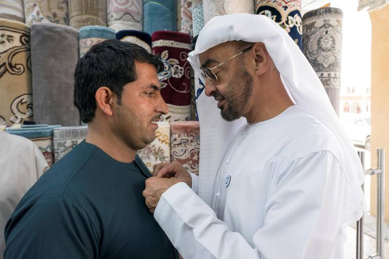 ABU DHABI, UNITED ARAB EMIRATES -  February 22, 2018: HH Sheikh Mohamed bin Zayed Al Nahyan, Crown Prince of Abu Dhabi and Deputy Supreme Commander of the UAE Armed Forces (R), puts a 'Year of Zayed' pin on a staff member at Al Safa Carpet shop, in the carpet market of the Mina Zayed Port.  ( Ryan Carter for the Crown Prince Court - Abu Dhabi ) ---