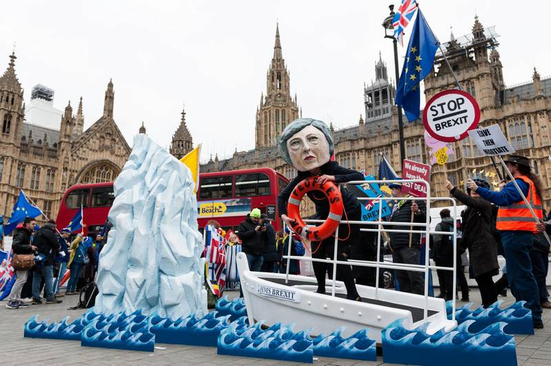 LONDON, UNITED KINGDOM - JANUARY 15: Pro-EU campaigners stage a stunt outside Houses of Parliament involving a model of a ship dubbed HMS Brexit steered by a demonstrator wearing a mask of Prime Minister Theresa May, clutching at People's Vote life ring, as the ship heads towards an iceberg representing fallout of Brexit. Activists from Best for Britain, Avaaz and Hope Not Hate campaigns call on MPs to reject Theresa May's EU Withdrawal deal during today's 'meaningful vote' and support a second referendum on Brexit. January 15, 2019 in London, England. (Photo credit should read Wiktor Szymanowicz / Barcroft Media via Getty Images)