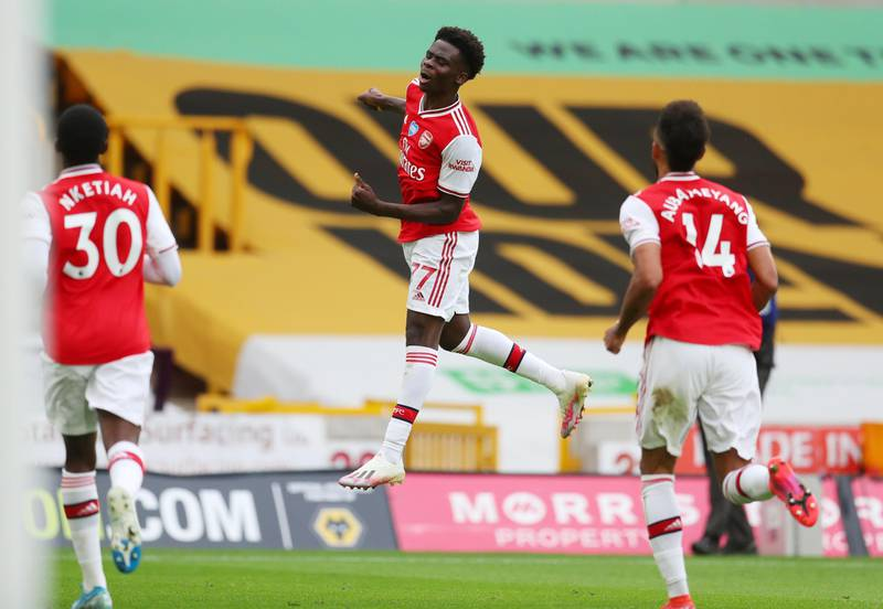 """Soccer Football - Premier League - Wolverhampton Wanderers v Arsenal - Molineux Stadium, Wolverhampton, Britain - July 4, 2020 Arsenal's Bukayo Saka celebrates scoring their first goal, as play resumes behind closed doors following the outbreak of the coronavirus disease (COVID-19) Catherine Ivill/Pool via REUTERS  EDITORIAL USE ONLY. No use with unauthorized audio, video, data, fixture lists, club/league logos or """"live"""" services. Online in-match use limited to 75 images, no video emulation. No use in betting, games or single club/league/player publications.  Please contact your account representative for further details."""