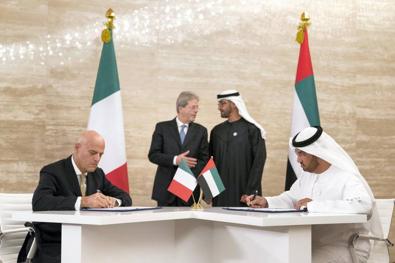 ABU DHABI, UNITED ARAB EMIRATES -  March 11, 2018: HH Sheikh Mohamed bin Zayed Al Nahyan, Crown Prince of Abu Dhabi and Deputy Supreme Commander of the UAE Armed Forces (back center R), and HE Paolo Gentiloni Silveri, Prime Minister of Italy (back center L), witness the signing of a memorandum of understanding (MOU), between Mubadala and Eni, at Al Shati Palace. Seen signing are HE Dr Sultan Ahmed Al Jaber, UAE Minister of State, Chairman of Masdar and CEO of ADNOC Group (R), and Claudio Descalzi CEO of Eni (L).   ( Ryan Carter for the Crown Prince Court - Abu Dhabi ) ---