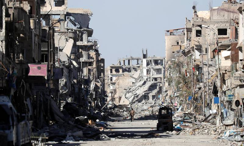 A fighter of Syrian Democratic Forces stands amidst the ruins of buildings near the Clock Square in Raqqa, Syria October 18, 2017. Picture taken October 18, 2017.     REUTERS/Erik De Castro