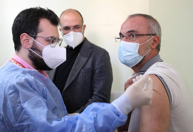 Lebanon's caretaker health minister Hamad Hassan (C) watches as a Lebanese teacher receives a Covid-19 AstraZeneca vaccine in Beirut on March 29, 2021. The country of over six million people has officially recorded more than 455,000 coronavirus cases and over 6,000 deaths. / AFP / ANWAR AMRO