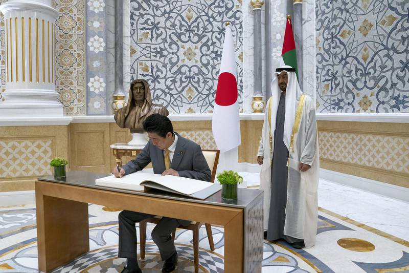 ABU DHABI, UNITED ARAB EMIRATES - January 13, 2020: HE Shinzo Abe, Prime Minister of Japan (L), signs the guestbook, during a reception, at Qasr Al Watan. Seen with HH Sheikh Mohamed bin Zayed Al Nahyan, Crown Prince of Abu Dhabi and Deputy Supreme Commander of the UAE Armed Forces (R).  ( Mohamed Al Hammadi / Ministry of Presidential Affairs ) ---