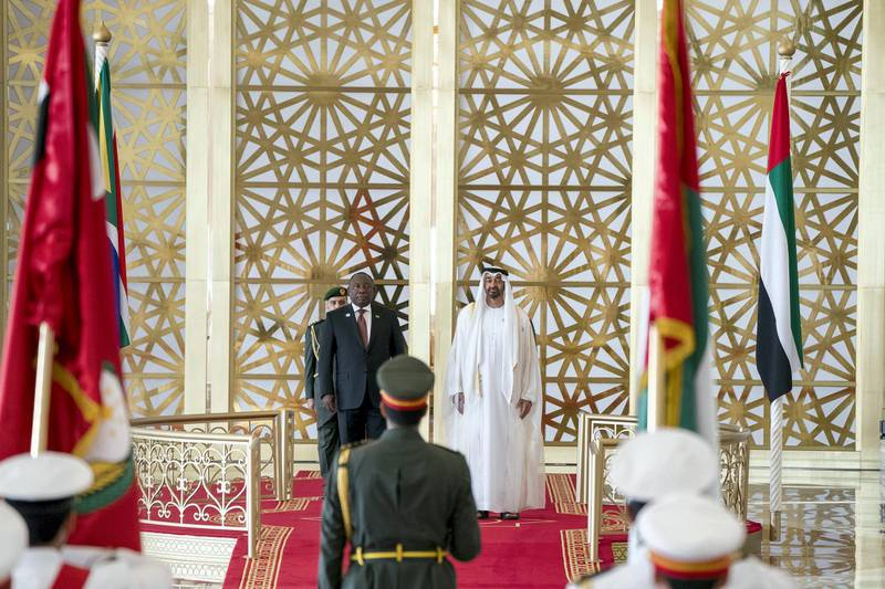ABU DHABI, UNITED ARAB EMIRATES - July 13, 2018: HH Sheikh Mohamed bin Zayed Al Nahyan Crown Prince of Abu Dhabi Deputy Supreme Commander of the UAE Armed Forces (R) and HE Cyril Ramaphosa, President of South Africa (L), stand for the UAE national anthem during a reception at the Presidential Airport.  ( Rashed Al Mansoori / Crown Prince Court - Abu Dhabi ) ---