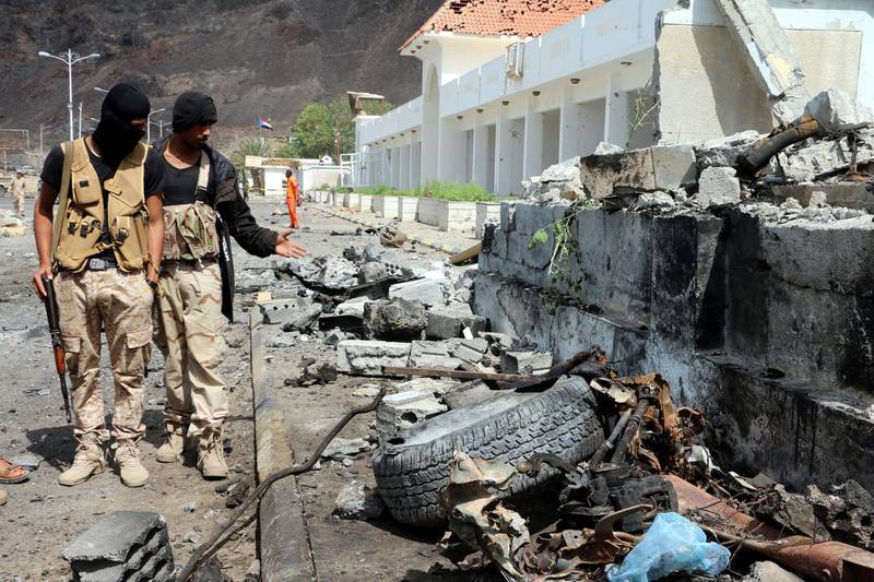 epa06563819 Yemeni soldiers inspect the site of car bomb attacks outside the headquarters of a counter-terrorism unit in the southern port city of Aden, Yemen, 25 February 2018. According to reports, at least 14 Yemenis were killed and 40 others wounded when two car suicide bombers struck the entrance of the headquarters of a counter-terrorism unit in Aden.  EPA/STRINGER