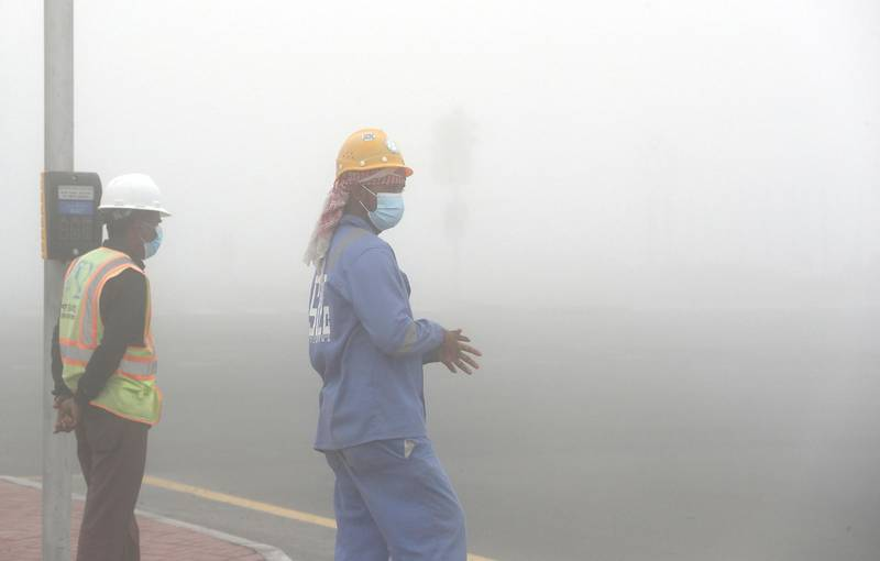 DUBAI, UNITED ARAB EMIRATES , April 08 – 2020 :- Workers during the early morning fog in Discovery Gardens area in Dubai. Dubai is conducting 24 hours sterilisation programme across all areas and communities in the Emirate and told residents to stay at home. UAE government told residents to wear face mask and gloves all the times outside the home whether they are showing symptoms of Covid-19 or not. (Pawan Singh/The National) For News/Online/Instagram/Standalone