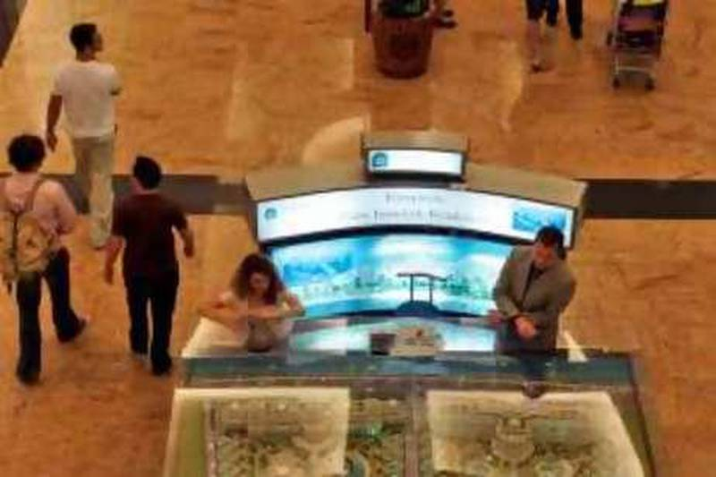 An Arab man looks at a development project's model as the others pass by at a shopping mall in Dubai, United Arab Emirates, Monday, Oct. 27, 2008. (AP Photo/Kamran Jebreili) *** Local Caption ***  XKJ101_Dubai_Property_Jitters.jpg