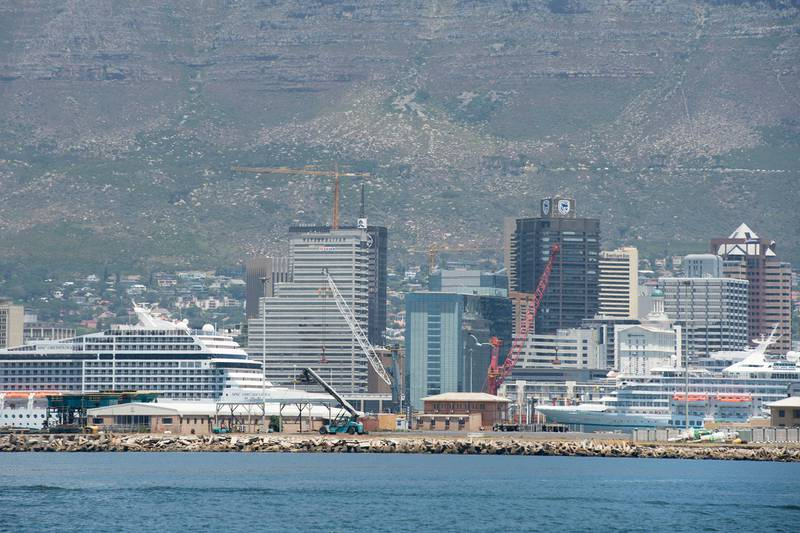 A view of cruise ships docked in the Cape Town Harbour, with the city and Table Mountain in the background on January 16, 2020, in Cape Town. (Photo by RODGER BOSCH / AFP)