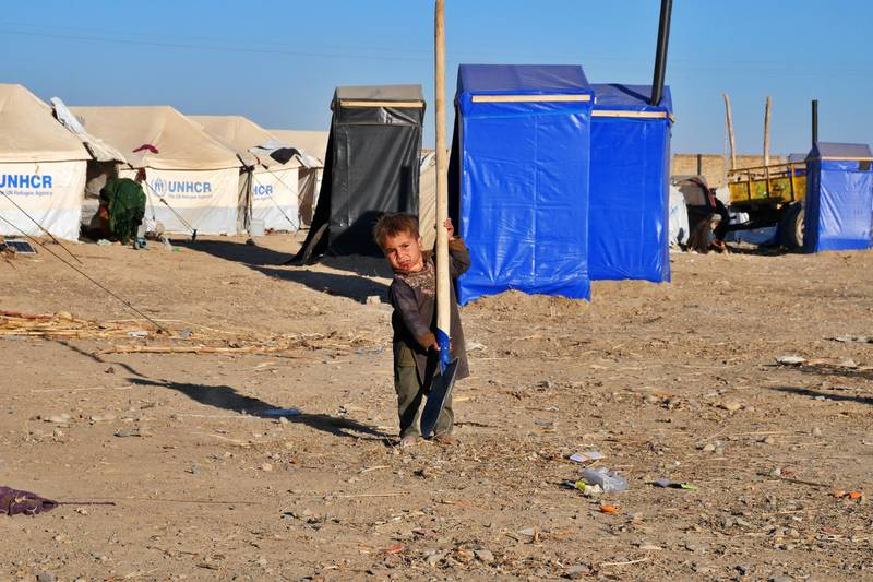 Pictured: A young boy occupies himself with a spade in an IDP camp located on the outskirts of Kandahar City.  Photo by Charlie Faulkner January 2021