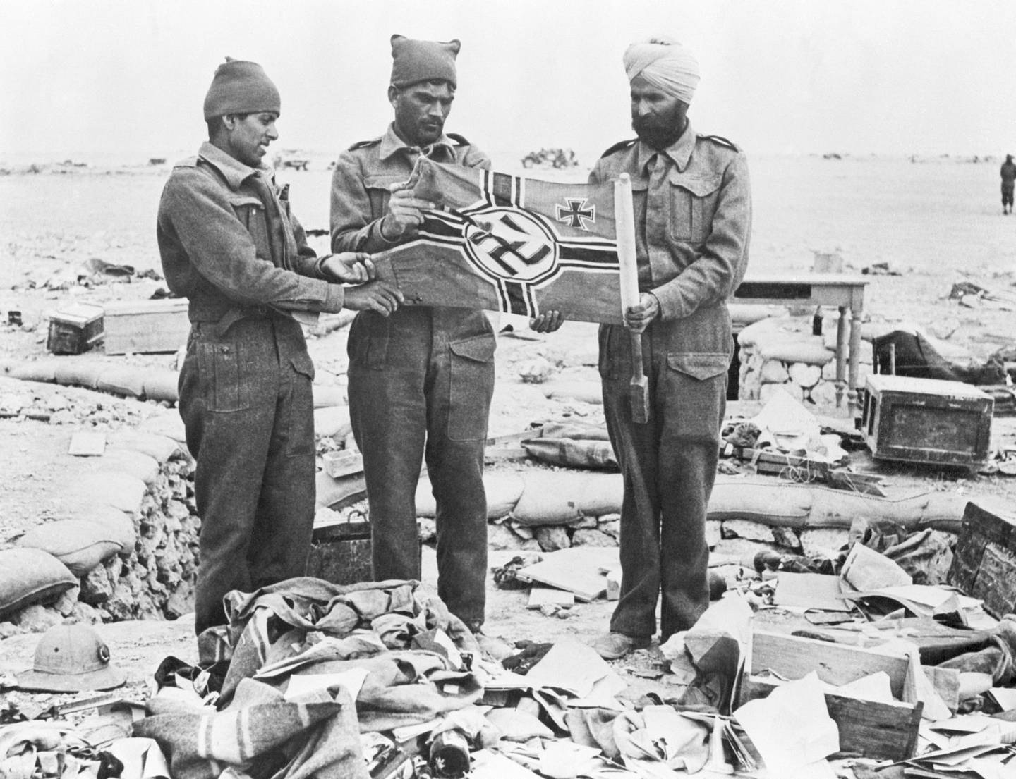 (Original Caption) 1/5/42-Libya: British Indian troops examine a Nazi flag found among the rubble in the shallow axis trenches on the Western Desert. This picture was made after the capture of Libyan Omar. (Bettmann / Corbis / Getty Images) *** Local Caption *** 2.514690706 rv21ma-books-raghavan01.jpg