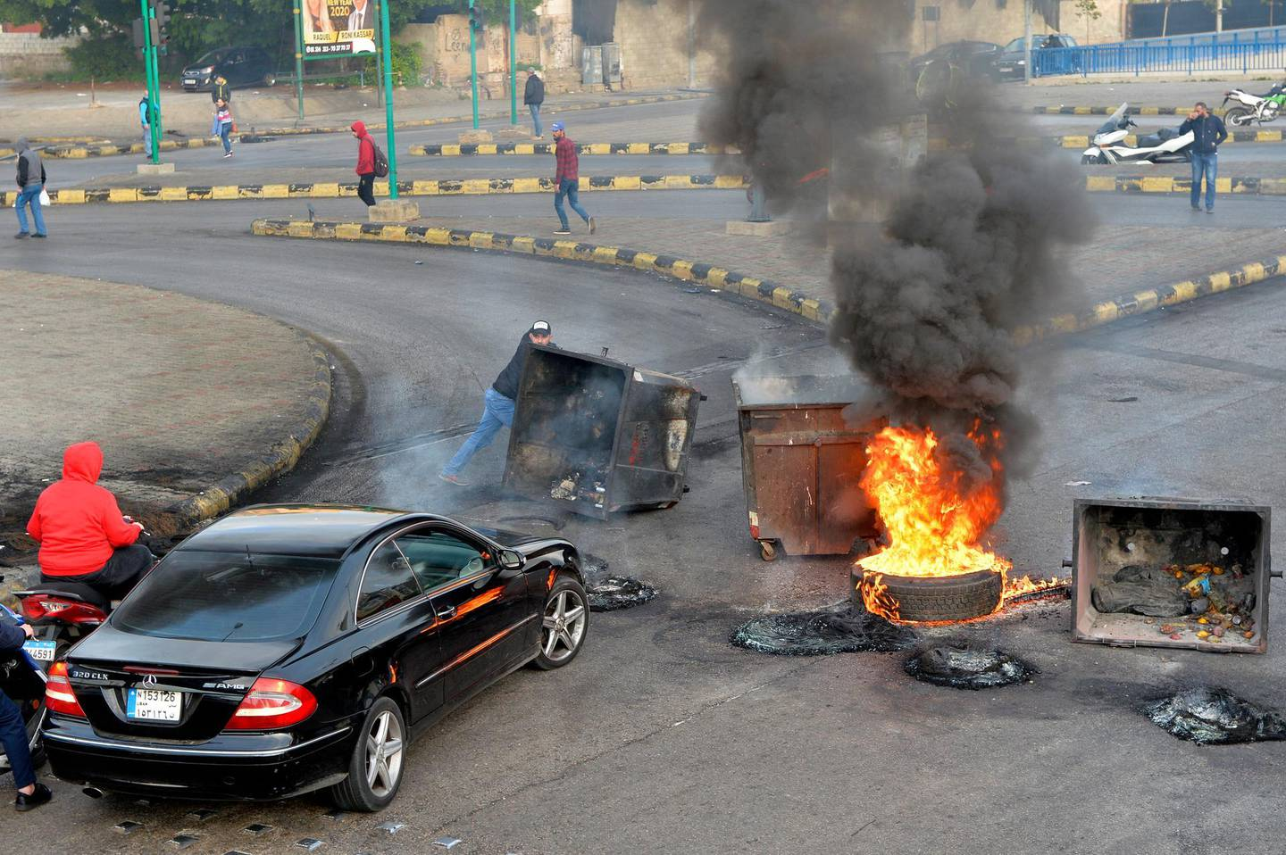 epa08087668 Supporters of outgoing Lebanese Prime Minister Hariri burn dumpsters and tires as they block a main highway in protest against the nomination of Hassan Diab as Prime Minister, in Beirut, Lebanon, 23 December 2019. The newly appointed Lebanese prime minister vowed on 19 December to form a government of experts within six weeks.  EPA/WAEL HAMZEH