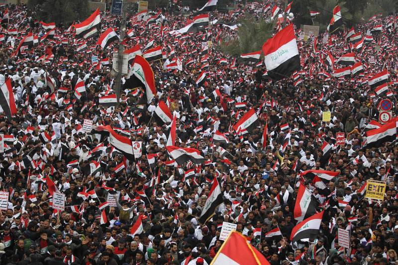 """Thousands of Iraqis, waving national flags, take to the streets in central Baghdad on January 24, 2020 to demand the ouster of US troops from the country. Thousands of supporters of volatile Iraqi cleric Moqtada Sadr gathered in the Iraqi capital on Friday for a """"million-strong"""" march to demand an end to the presence of US forces in Iraq, putting the protest-hit capital on edge. The march has rattled the separate, months-old protest movement that has gripped Baghdad and the Shiite-majority south since October, demanding a government overhaul, early elections and more accountability. / AFP / AHMAD AL-RUBAYE"""