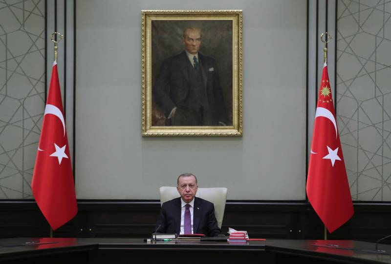 """Turkey's President Recep Tayyip Erdogan, backdropped by a painting depicting modern Turkey's founder Mustafa Kemal Ataturk, chairs his government's cabinet in Ankara, Turkey, Monday, April 26, 2021. Erdogan said he was """"highly saddened"""" by U.S. President Joe Biden's decision to mark as genocide the mass deportations and massacres of Armenians in the early 20th century Ottoman Empire, calling it baseless and unjust. (Turkish Presidency via AP)"""