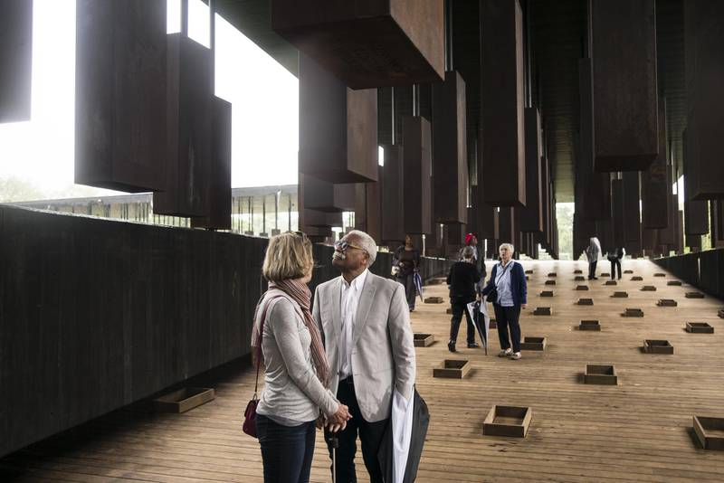 """MONTGOMERY, AL - APRIL 26: Ed Sykes (center), 77, visits the National Memorial For Peace And Justice on April 26, 2018 in Montgomery, Alabama. Sykes, who has family in Mississippi, was distraught when he discovered his last name in the memorial, three months after finding it on separate memorial in Clay County, Mississippi. """"This is the second time I've seen the name Sykes as a hanging victim. What can I say?"""" Sykes, who now lives in San Francisco, plans to investigate the lynching of a possible relative at the Equal Justice Initiative headquarters in Montgomery before returning to California. The memorial is dedicated to the legacy of enslaved black people and those terrorized by lynching and Jim Crow segregation in America. Conceived by the Equal Justice Initiative, the physical environment is intended to foster reflection on America's history of racial inequality.   Bob Miller/Getty Images/AFP"""