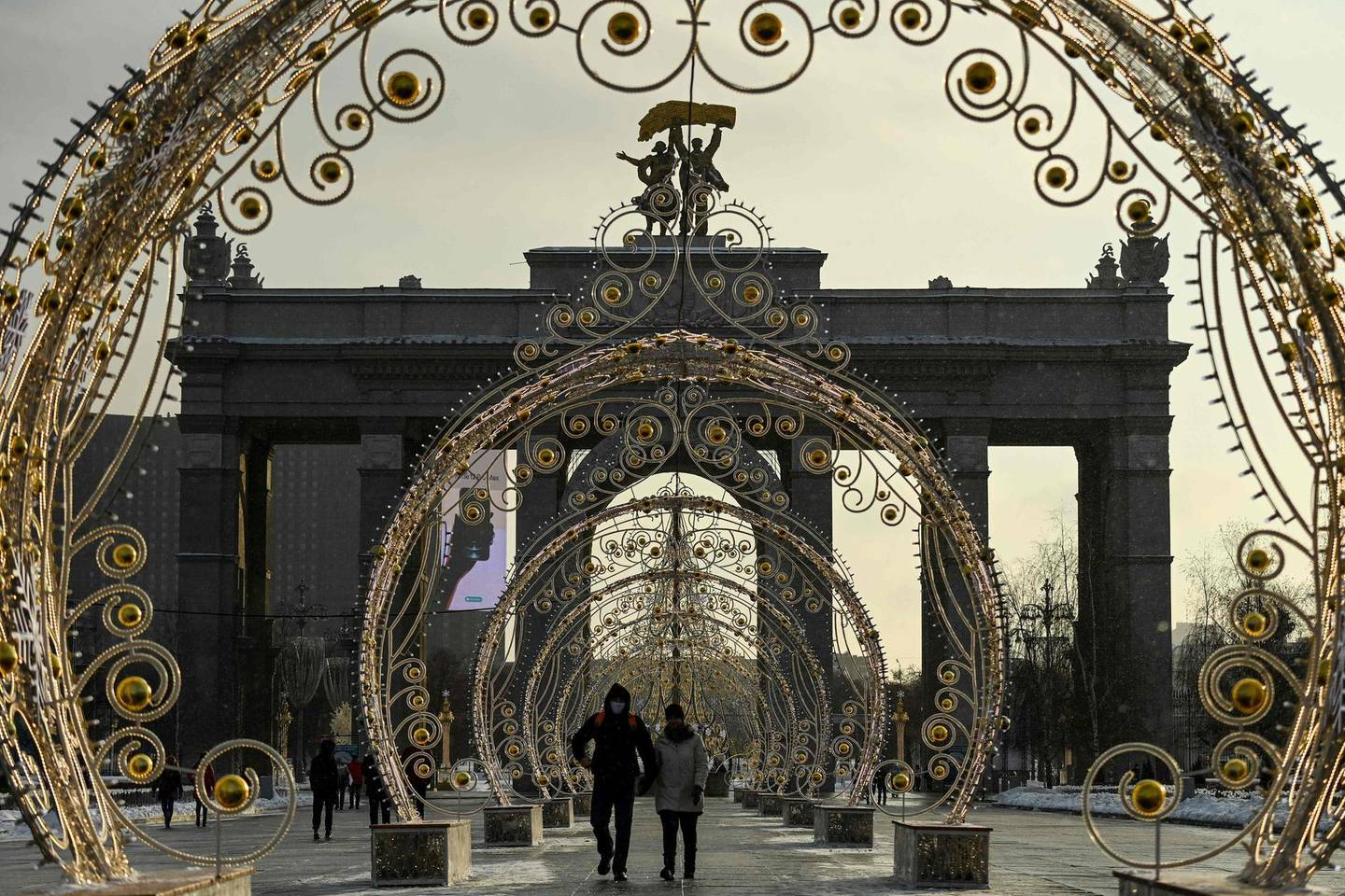 People wearing protective facemask walk past festive decorations set for Christmas and the upcoming New Year's celebrations, in Moscow on December 27, 2020, amid the ongoing Covid-19, (the novel coronavirus) pandemic. Russia confirmed 28,284 new Covid-19 cases on December 27. / AFP / Kirill KUDRYAVTSEV