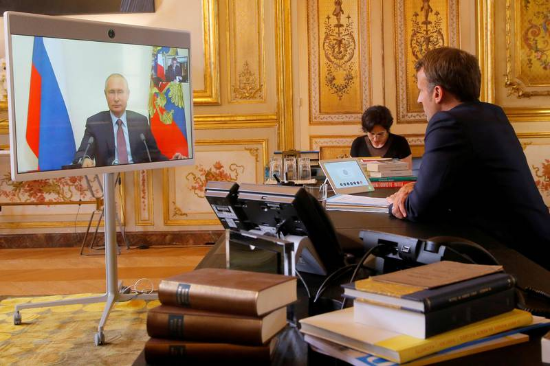 French President Emmanuel Macron talks with Russian President Vladimir Putin during a video conference at the Elysee Palace in Paris, France, June 26, 2020. Michel Euler/Pool via REUTERS