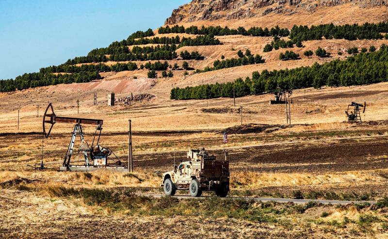 A US military armoured vehicle drives in a patrol past a pumpjack operating at an oil well in Rumaylan (Rmeilan) in Syria's northeastern Hasakeh province on November 6, 2019.  / AFP / Delil SOULEIMAN