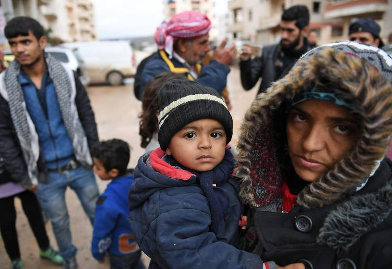 A Syrian woman carries a child as she arrives with others who fled from the town of Jandairis in the southwestern corner of the Afrin enclave, where Turkey and allied rebels have been conducting an offensive to oust Kurdish militias, in the city of Afrin on January 25, 2018. Jandairis has been heavily targeted by Turkish air strikes and rockets as it sits close to the border and near a front line with pro-Ankara rebels. / AFP PHOTO / George OURFALIAN