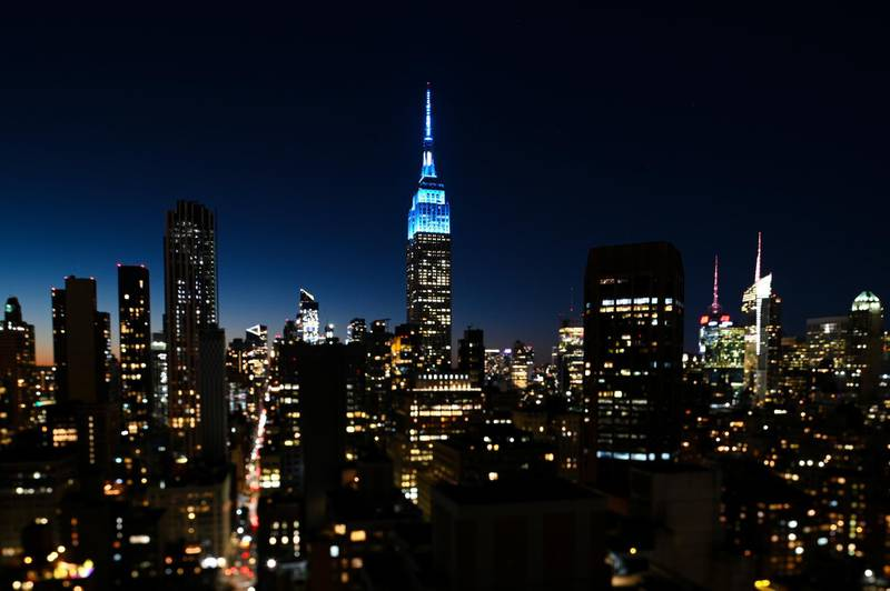 In a photo taken with a perspective control lens, the Empire State Building is illuminated light blue, Thursday, Oct. 8, 2020, in New York, in honor of what would've been John Lennon's 80th birthday, on Friday. (Photo by Evan Agostini/Invision/AP)