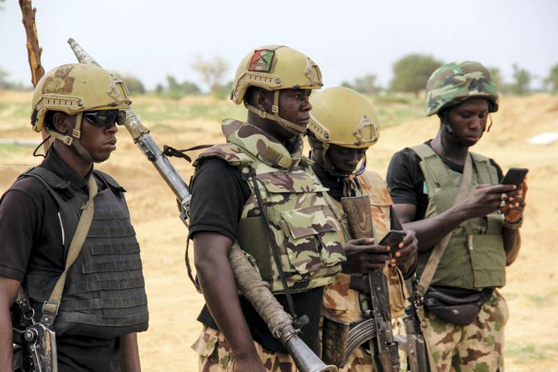 Nigerian Army soldiers stand at a base in Baga on August 2, 2019. - Intense fighting between a regional force and the Islamic State group in West Africa (ISWAP) has resulted in dozens of deaths, including at least 25 soldiers and more than 40 jihadists, in northeastern Nigeria. ISWAP broke away from Boko Haram in 2016 in part due to its rejection of indiscriminate attacks on civilians. Last year the group witnessed a reported takeover by more hardline fighters who sidelined its leader and executed his deputy. The IS-affiliate has since July 2018 ratcheted up a campaign of attacks against military targets. (Photo by AUDU MARTE / AFP)