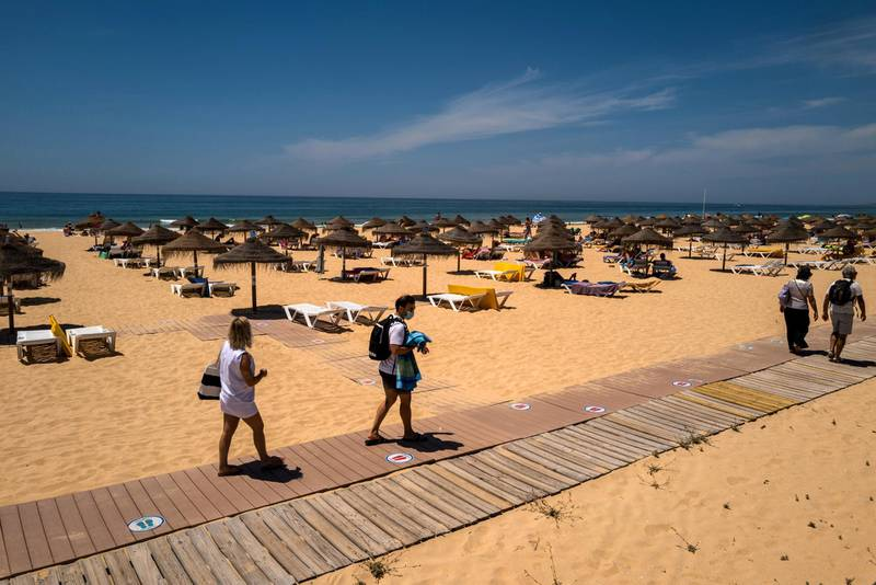Beachgoers make their way onto the sand at Falesia Beach in Vilamoura, Portugal, on Sunday, May 30, 2021. Portugal is likely to raise its economic growth forecast for this year to close to 5% as tourists help boost the recovery and Europe's Covid-19 vaccination campaign advances. Photographer: Jose Sarmento Matos/Bloomberg