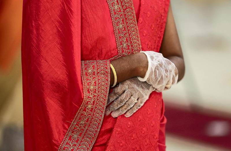 DUBAI, UNITED ARAB EMIRATES , October 26– 2020 :- One of the relative wearing gloves during the marriage ceremony of Justin George (groom) and Jubee Vargheese (bride) held at the St. Thomas Orthodox Cathedral in Dubai. Relatives and friends wearing protective face mask and gloves as a preventive measure against the spread of coronavirus and maintaining social distance during the ceremony.  (Pawan Singh / The National) For News/Online/Instagram. Story by Kelly