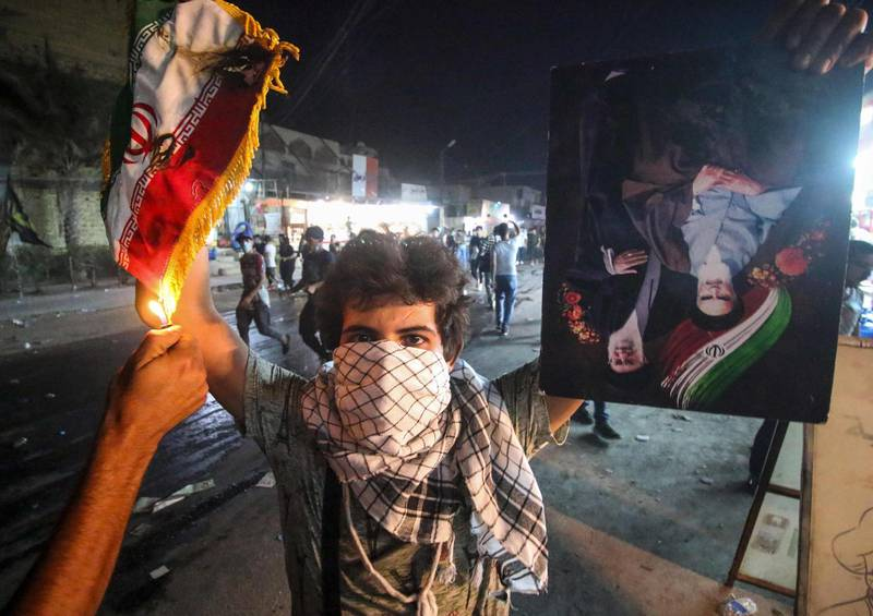 TOPSHOT - An Iraqi protester holds up an Iranian flag as another sets it on fire for him, next to a portrait depicting Iran's former and current Supreme Leaders Ayatollah Khomeini and Khamenei, during demonstrations against the government and the lack of basic services in Basra on September 7, 2018. - Iraqi protesters on Friday torched the Iranian consulate in the southern city of Basra on September 7 in fresh demonstrations over poor public services after parliament called for an emergency session on the unrest. (Photo by Haidar MOHAMMED ALI / AFP)