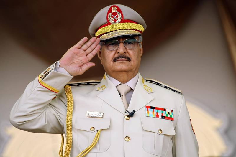 """(FILES) In this file photo taken on May 7, 2018, Libyan Strongman Khalifa Haftar salutes during a military parade in the eastern city of Benghazi, during which he announced a military offensive to take from """"terrorists"""" the city of Derna, the only part of eastern Libya outside his forces' control. Libyan strongman Khalifa Haftar, whose forces have been battling to capture the seat of the UN-recognised government in Tripoli since April 2019, has said he is open to dialogue after repeatedly rejecting UN calls for talks. """"When all is said and done, we need dialogue and we need to sit down"""" at the negotiating table, Hafar said in a statement issued late on September 25 on the eve of a special session on Libya on the sidelines of the UN General Assembly in New York. / AFP / Abdullah DOMA"""