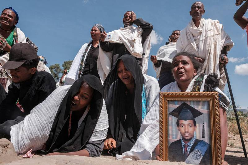 TOPSHOT - People react as they stand next to a mass grave containing the bodies of 81 victims of Eritrean and Ethiopian forces, killed during violence of the previous months, in the city of Wukro, north of Mekele, on February 28, 2021. Every phase of the four-month-old conflict in Tigray has brought suffering to Wukro, a fast-growing transport hub once best-known for its religious and archaeological sites.  Ahead of federal forces' arrival in late November 2020, heavy shelling levelled homes and businesses and sent plumes of dust and smoke rising above near-deserted streets.  Since then the town has been heavily patrolled by soldiers, Eritreans at first, now mostly Ethiopians, whose abuses fuel a steady flow of civilian casualties and stoke anger with Nobel Peace Prize-winner Abiy. / AFP / EDUARDO SOTERAS