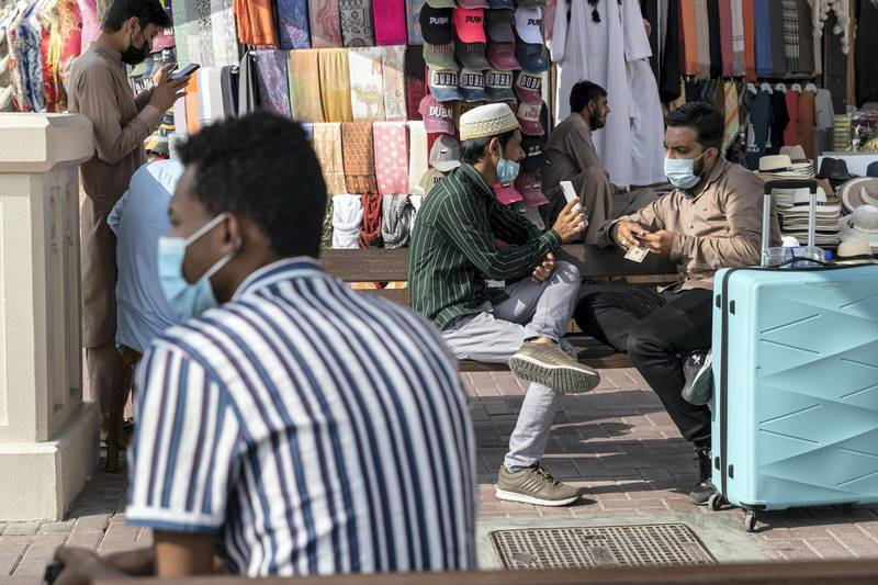 DUBAI, UNITED ARAB EMIRATES. 25 FEBRUARY 2021. COVID - 19 Standalone. Deira souk during the time of Covid. Men talk and wait while wearing face mask in the Abra station near the Spice souk. (Photo: Antonie Robertson/The National) Journalist: Nick Webster. Section: National.