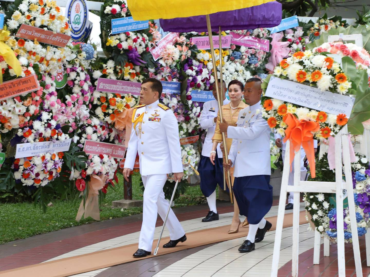 Thailand's King Maha Vajiralongkorn and Queen Suthida arrive at the Siriraj Hospital in Bangkok, Thailand, Thursday, Sept. 24, 2020. King Maha Vachiralongkorn and Queen Suthida are presiding over the wreath laying ceremony on Mahidol day, which the memorable event to his grandfather who was considered as the founding father of Thailand's modern medicine. (Mitichon Newspaper via AP)