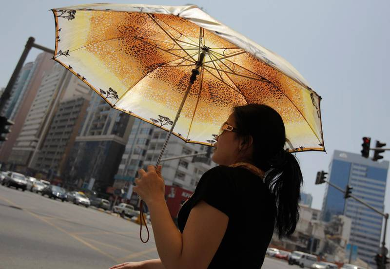 ABU DHABI, UNITED ARAB EMIRATES - May 30, 2009: A lady takes refuge from the sun with an umbrella, it was a hot day today in Abu Dhabi. ( Ryan Carter / The National )*** stock, hot, heat, weather, sun,  *** Local Caption ***  RC008-HeatHot.JPGRC008-HeatHot.JPGRC008-HeatHot.JPG