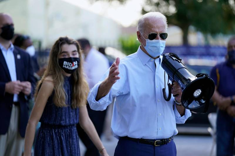 Democratic presidential candidate former Vice President Joe Biden, accompanied by his granddaughter Natalie Biden, speaks to people outside a campaign victory center, Thursday, Oct. 29, 2020, in Fort Lauderdale, Fla. (AP Photo/Andrew Harnik)