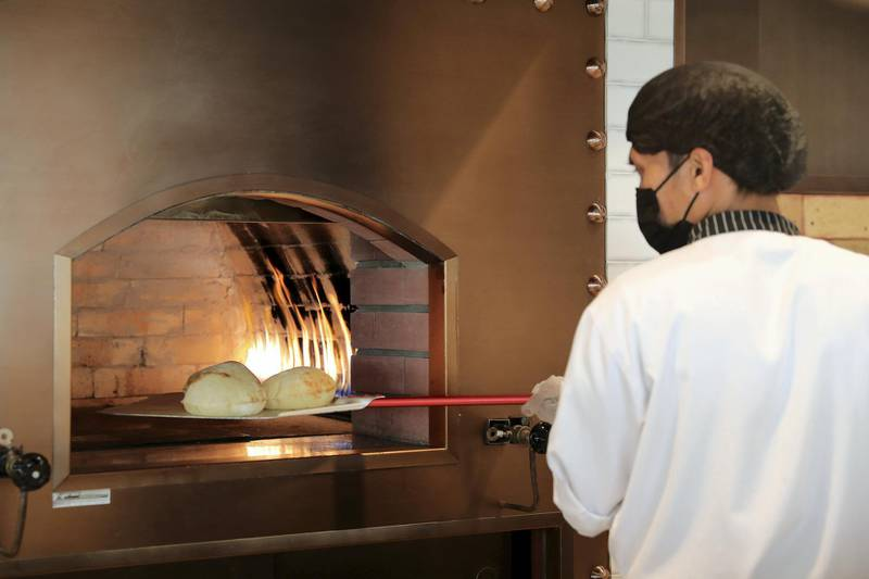 Staff preparing fresh breads at the Grand Beirut restaurant at Dubai Digital Park in Dubai Silicon Oasis in Dubai on June 22,2021. Pawan Singh / The National. Story by Janice Rodrigues
