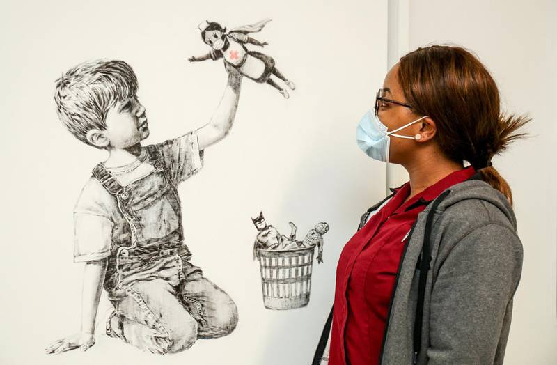 """A handout picture recieved from University Hospital Southampton on May 7, 2020 shows a member of staff posing with an artwork by street artist Banksy called """"Game Changer"""", showing a boy playing with a nurse superhero toy with figures of Batman and Spiderman discarded in a basket as a tribute to NHS staff who are continuing to work during the COVID-19 pandemic, on a wall at the University Hospital Southampton, southern England. - A new artwork by Banksy in honour of Britain's health service has gone on display in a hospital, paying tribute to medics battling the coronavirus pandemic in the second hardest-hit country. The street artist also posted an image of the work on Instagram, which shows a boy in dungarees playing with a figurine of a nurse in a superhero cape. (Photo by Stuart MARTIN / various sources / AFP) / RESTRICTED TO EDITORIAL USE - MANDATORY CREDIT """"AFP PHOTO / UNIVERSITY HOSPITAL SOUTHAMPTON / STUART MARTIN """" - NO MARKETING - NO ADVERTISING CAMPAIGNS - MANDATORY MENTION OF ARTIST UPON PUBLICATION - DISTRIBUTED AS A SERVICE TO CLIENTS"""