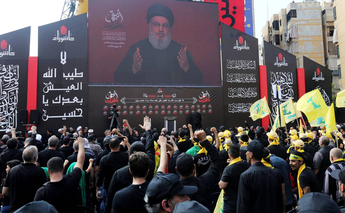 FILE PHOTO: Lebanon's Hezbollah leader Sayyed Hassan Nasrallah gestures as he addresses his supporters via a screen during the religious procession to mark the Shi'ite Ashura ceremony, in Beirut, Lebanon September 10, 2019. REUTERS/Aziz Taher -/File Photo