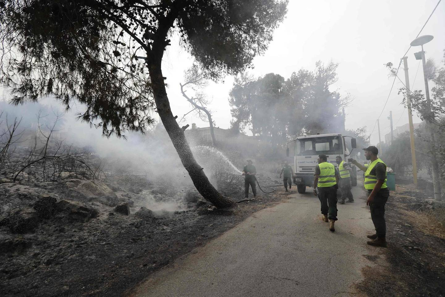 Firefighters extinguish flames in a  forest near the village of Meshref in Lebanon's Shouf mountains, southeast of the capital Beirut, on October 15, 2019. Flames devoured large swaths of land in several Lebanese and Syrian regions. The outbreak coincided with high temperatures and strong winds, according to the official media in both countries. / AFP / JOSEPH EID