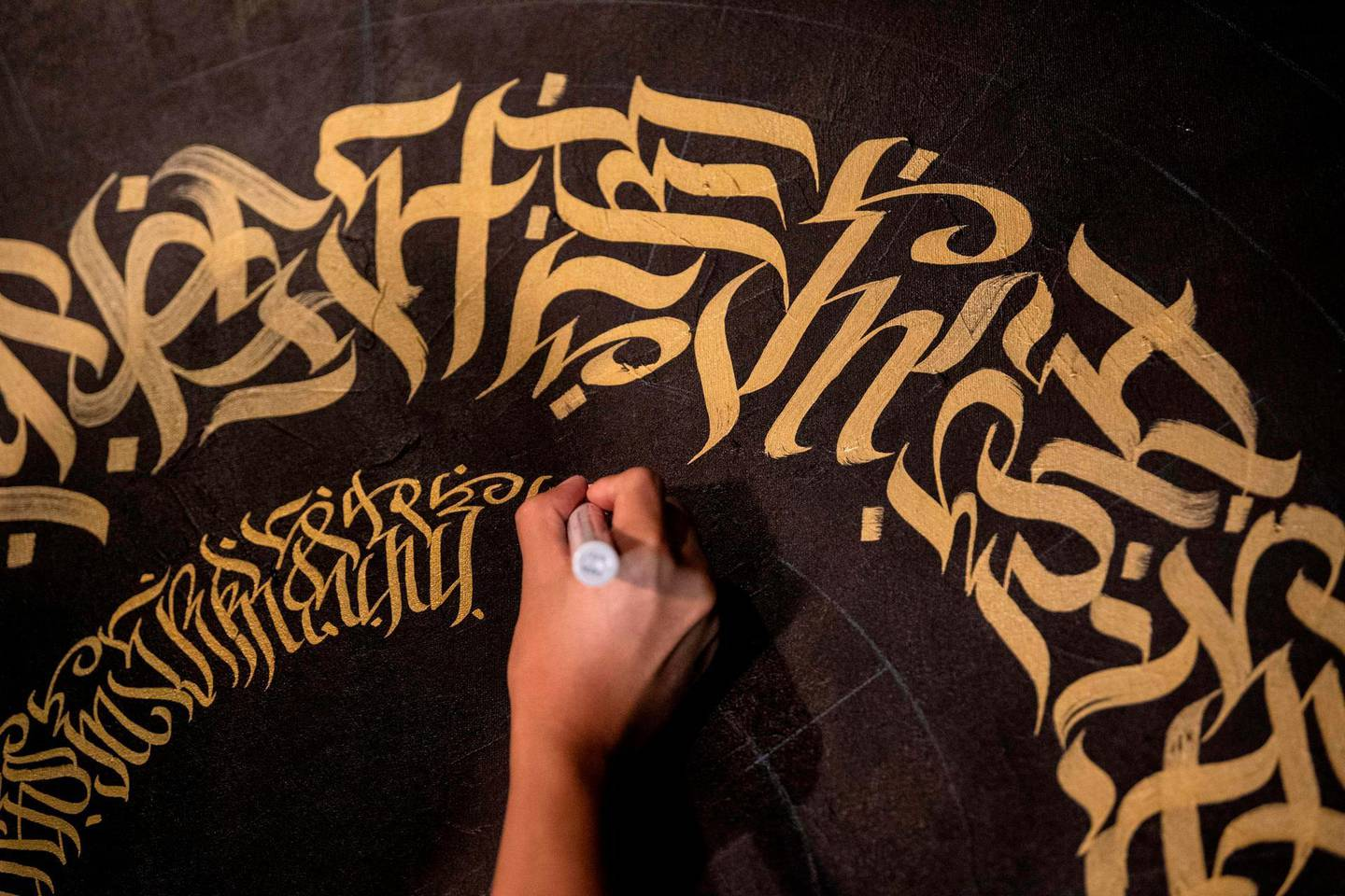 This photo taken on June 22, 2019 shows artist Taipan Lucero doing calligraphy using the indigenous scriptknown as Baybayin, used before Spanish colonisation in 1521, at an event in Manila. From tattoos, shirts, and artworks to a computer font and mobile apps, Baybayin found a rebirth among millennials and professionals learning its 17 characters beyond the marginal mention in history class.   - TO GO WITH AFP STORY: Philippines-culture-language, FEATURE by Ayee MACARAIG  / AFP / Noel CELIS / TO GO WITH AFP STORY: Philippines-culture-language, FEATURE by Ayee MACARAIG
