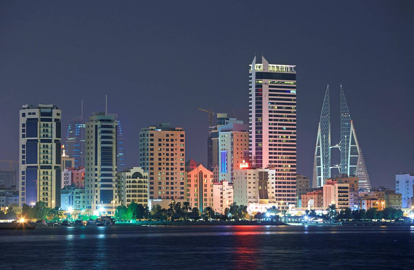 Cityscape of the hotels, skyscrapers and development along the 'Al Corniche' and the 'Diplomatic Area' of Manama in Bahrain illuminated at night.