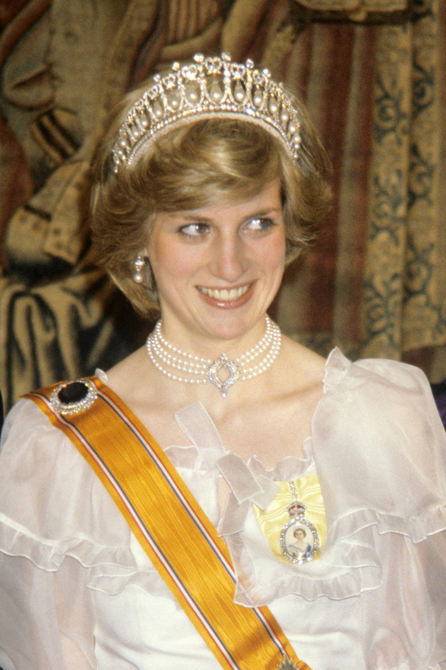 The Princess of Wales at a banquet for the British royal family given by Queen Beatrix and Prince Claus of the Netherlands at Hampton Court Palace. The Princess wears the sash of the House Order of Orange, presented to her by Queen Beatrix. PA Images via Reuters