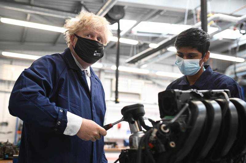 Britain's Prime Minister Boris Johnson (L) assists in an engine repair at the Automotive shop during a visit to Kirklees College Springfield Sixth Form Centre in Dewsbury, northern England on June 18, 2021. / AFP / POOL / Oli SCARFF