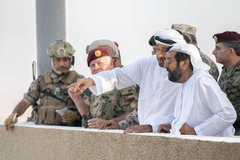 AL DHAFRA REGION, ABU DHABI, UNITED ARAB EMIRATES - June 26, 2019: (R-L) HH Sheikh Tahnoon bin Mohamed Al Nahyan, Ruler's Representative in Al Ain Region, HH Sheikh Mohamed bin Zayed Al Nahyan, Crown Prince of Abu Dhabi and Deputy Supreme Commander of the UAE Armed Forces and HM King Abdullah II, King of Jordan, attend the UAE and Jordan joint military drill, Titled 'Bonds of Strength', at Al Hamra Camp.  ( Rashed Al Mansoori / Ministry of Presidential Affairs ) ---