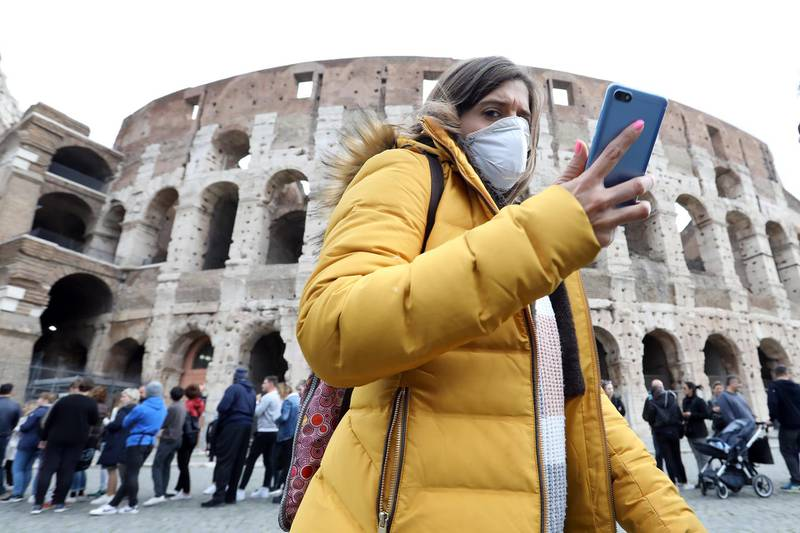 A pedestrian wearing a protective face masks walks past the Colosseum in Rome, Italy, on Tuesday, Feb. 25, 2020. Italy appears never far from a recession, and the spread of the coronavirus may just tip it back into the danger zone. Photographer: Alessia Pierdomenico/Bloomberg