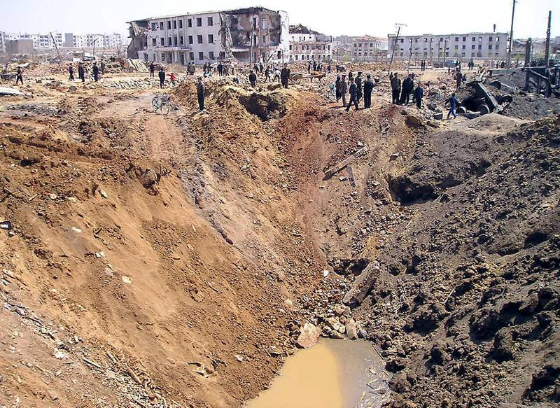 Rescuers pass by a large crater caused by a catastrophic explosion at the railway station in Ryongchon, North Korea, 24 April 2004.   Foreign aid workers reaching the site of the North Korean train explosion on Saturday reported a scene of utter devastation and confirmed about half of the 154 victims were children.                                  AFP PHOTO/WFP (Photo by WFP / WFP / AFP)
