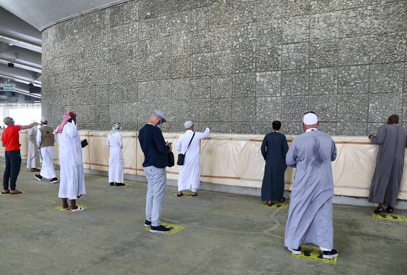 Muslim pilgrims, clad in face masks and keeping a safe distance from each other due to the coronavirus pandemic, throw pebbles as part of the symbolic al-A'qabah (stoning of the devil ritual) at the Jamarat Bridge during the Hajj pilgrimage in Mina, near Saudi Arabia's holy city of Mecca, on August 1, 2020. - Massive crowds in previous years triggered deadly stampedes during the ritual, but this year only up to 10,000 Muslims are taking part after millions of international pilgrims were barred because of the covid-19 pandemic crisis. (Photo by - / AFP)