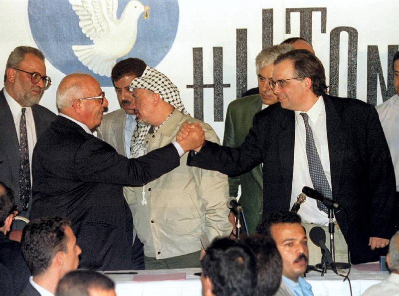 Palestinian and Israeli top negotiators Abu Ala [L] and Uri Savir [R] shake hands after signing the second phase of the Oslo peace accords September 24. PLO chairman Yasser Arafat is in the middle speaking to team member Sait Barecat, (L), after eight days of talks. The Oslo peace accords second phase will give the Palestinian self-rule of the West Bank