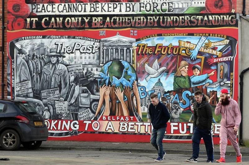 Men walk past a mural on the Newtownards Road in Belfast on January 25, 2017. Northern Ireland will hold snap elections on March 2, 2017 in a bid to resolve its worst political crisis in years after the power-sharing executive collapsed on January 16, 2017. Under the rules of the power-sharing government, which was set up as part of the peace process, the January 10, 2107 resignation of Deputy First minister Martin McGuinness, of Sinn Fein, forced First Minister Arlene Foster, from the rival Democratic Unionist Party, to also step down. / AFP PHOTO / Paul FAITH