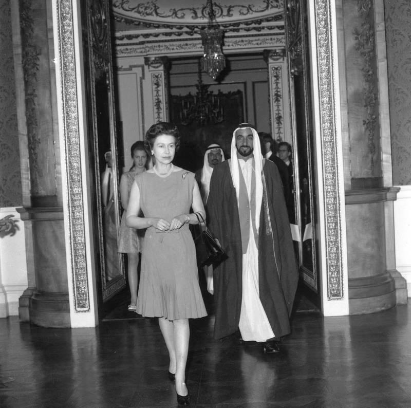 13th June 1969:  Queen Elizabeth II leading Sheikh Zayed, ruler of Abu Dhabi through Buckingham Palace, London.  (Photo by Tim Graham/Fox Photos/Getty Images)