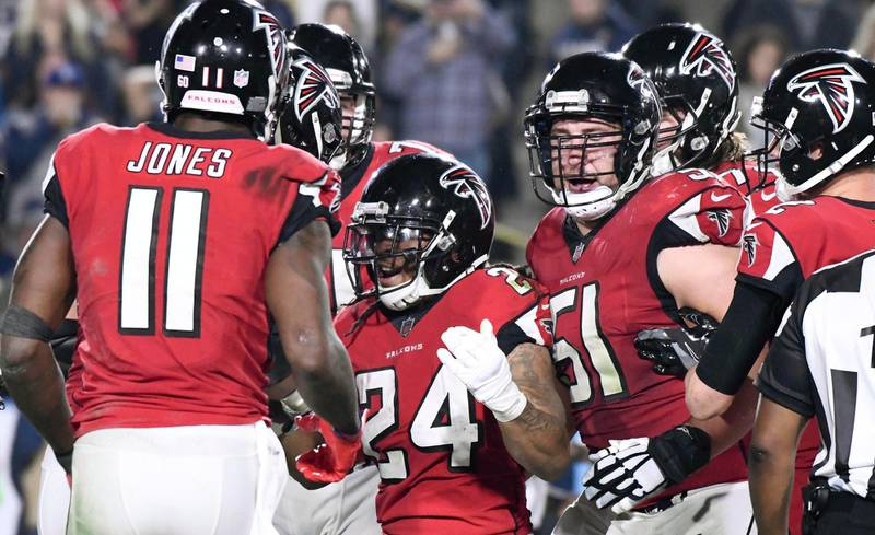Jan 6, 2018; Los Angeles, CA, USA; Atlanta Falcons running back Devonta Freeman (24) celebrates with offensive tackle Jake Matthews (70) and center Alex Mack (51) after scoring a touchdown in the second quarter against the Los Angeles Rams in the NFC Wild Card playoff football game at Los Angeles Memorial Coliseum. Mandatory Credit: Robert Hanashiro-USA TODAY Sports