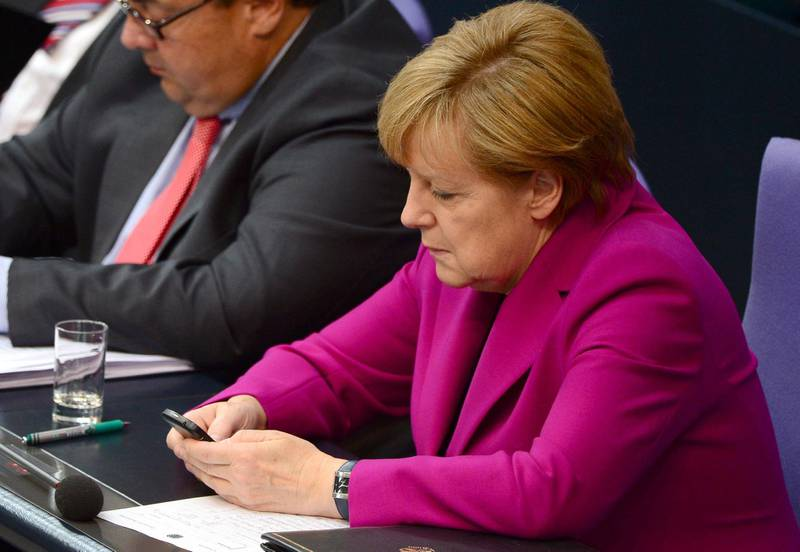 (FILES) This file photo taken on June 4, 2014 shows German Chancellor Angela Merkel holding her mobile phone during a session of the Bundestag Lower House of parliament in Berlin. The US spied on top politicians in Europe, including German Chancellor Angela Merkel, from 2012 to 2014 with the help of Danish intelligence, Danish and European media reported on May 30, 2021. / AFP / John MACDOUGALL